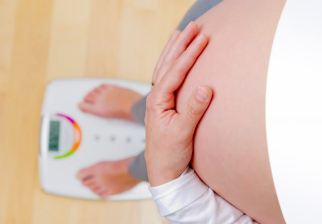 Беременная женщина стоит на весах