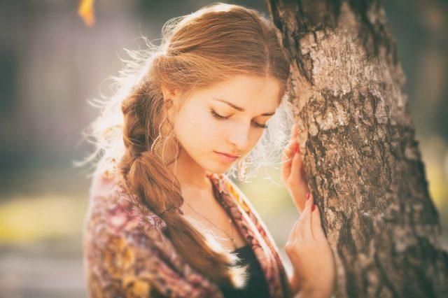 Женщина грустит возле дерева
