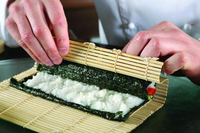 Повар сворачивает ролл из суши