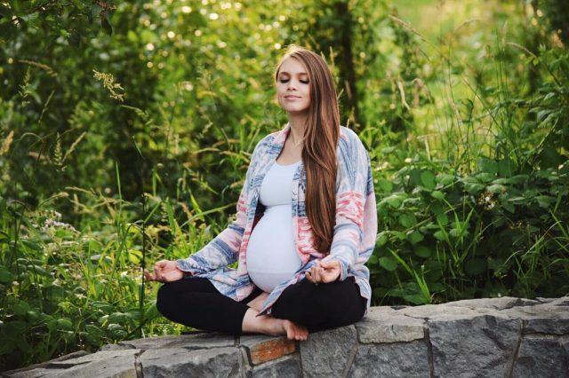 Красивая беременная девушка в позе лотоса на природе
