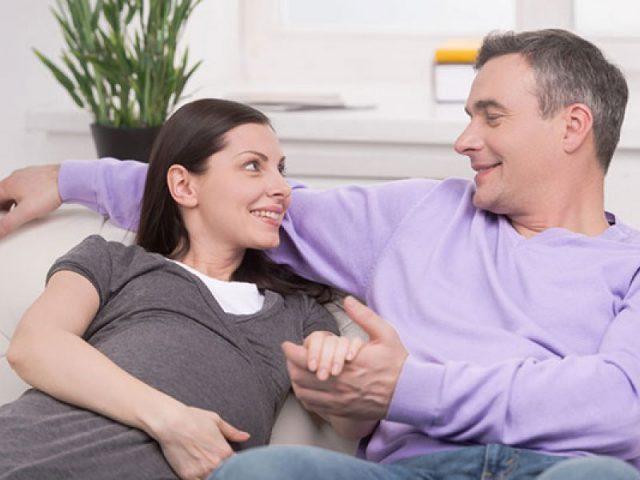Беременная с мужем сидят на диване