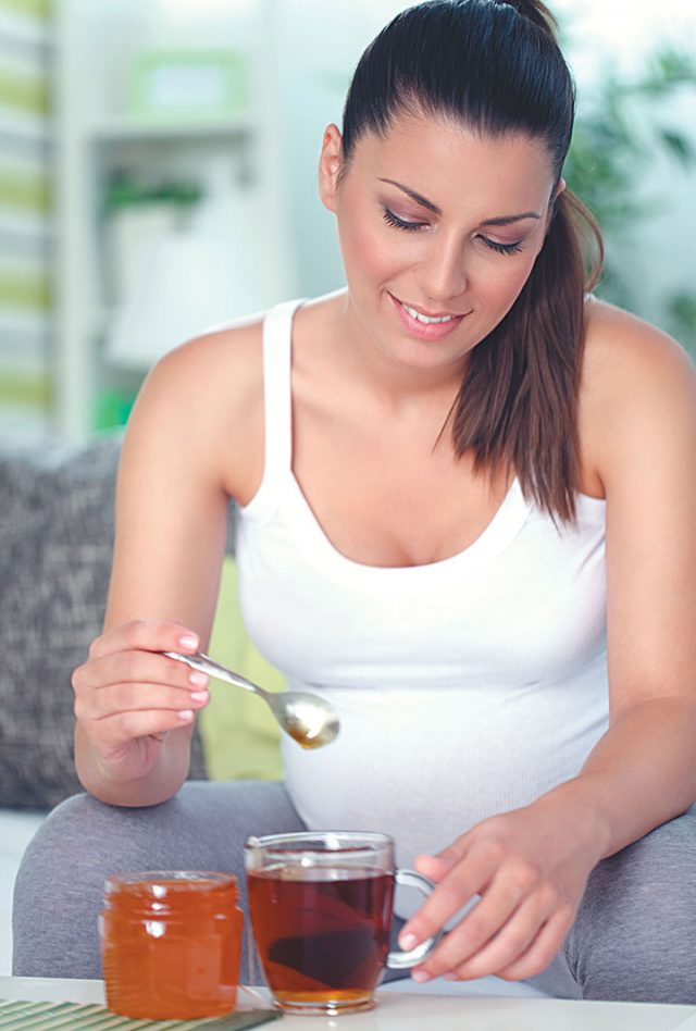 Беременная женщина кладёт мёд в чай