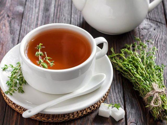 Чашка чёрного чая с веточками чабреца