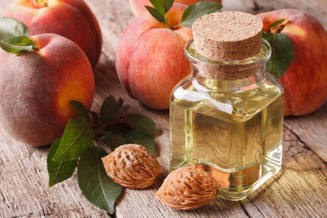 Свежие персики и масло во флаконе
