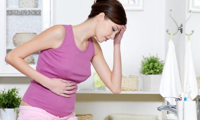 Беременная держится за живот и голову
