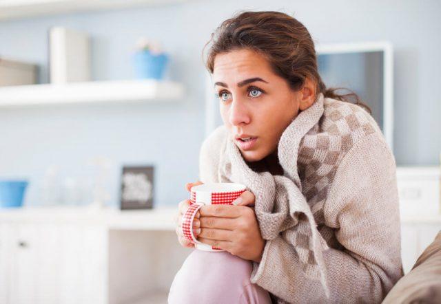 женщина сидит, съёжившись, в тёплой кофте и со стаканом в руках