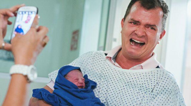 Мужчина с младенцем на руках кричит