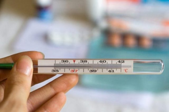 Термометр в женской руке — шкала на отметке 38,8 °С