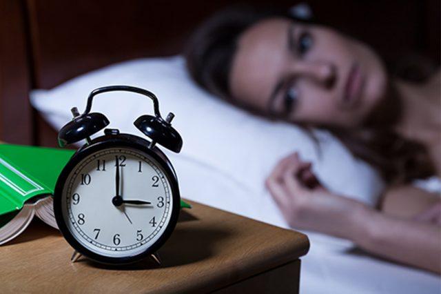 Женщина лежит в кровати и смотрит на будильник